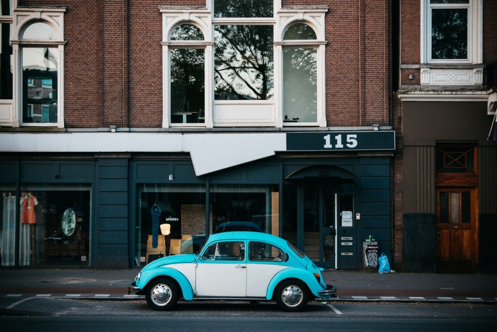 Pale blue classic VW Beetle parked by the roadside